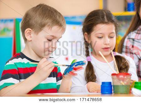 Cute preschool children painting with their palms at kindergarten