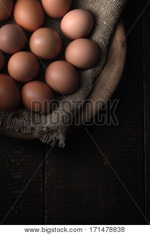 Chicken eggs in the wooden bowl top view