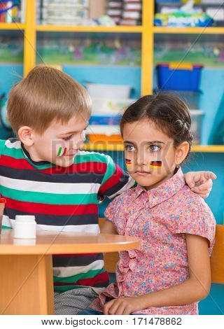 Little children in language camp with flags on cheeks