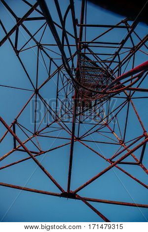 High metal tower on blue sky. Large scale