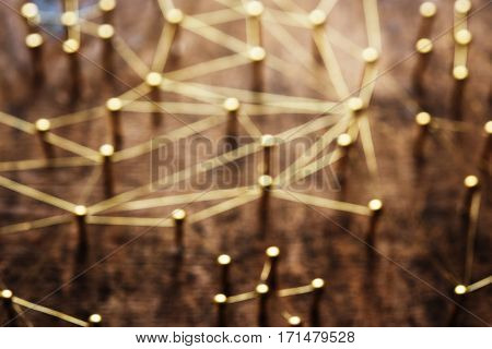 Linking entities, blurred background, or off-focus background. Network, networking, social media, internet communication abstract. Web of gold wires on rustic wood with vintage taste.