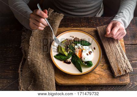 Woman eating poached egg with avocado cream top view
