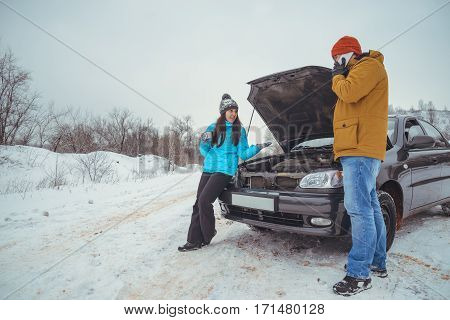 couple on the road with broken car woman angry on man winter cold