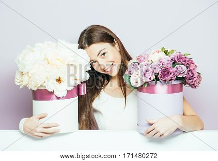 Sexy young pretty woman or cute smiling girl with long brunette hair with rose and peony flowers bouquet boxes on lilac background