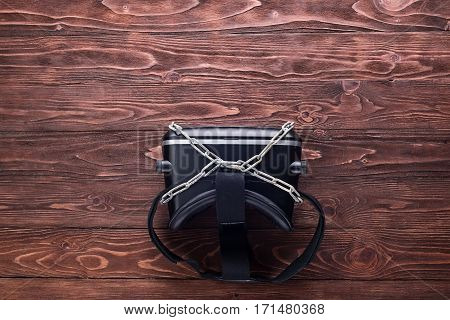 Virtual reality device and metal chain on wooden table.Top view