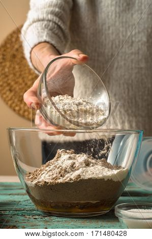 Adding flour in glass bowl for pancakes preparation vertical