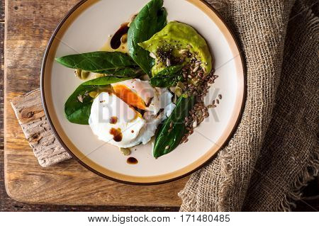 Poached egg with avocado cream and spinach on the wooden background top view