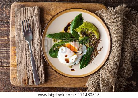Poached egg with avocado cream and spinach on the old wooden table