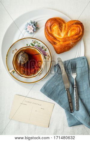 Sweet bun with cup of tea on the white table vertical