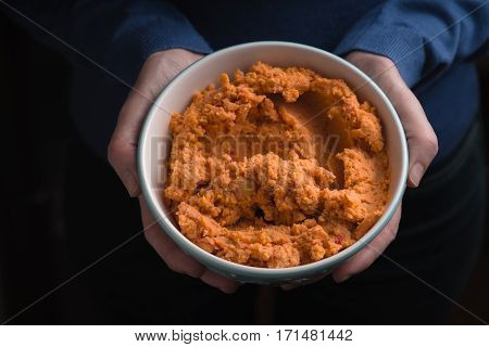 Bowl with hummus on the hands top view