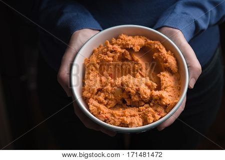 Hummus in the bowl in the woman's hands