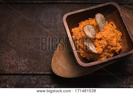 Hummus in the wooden bowl on the old metal background horizontal