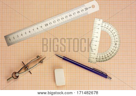 On graph paper are compasses protractor ruler eraser and a pencil