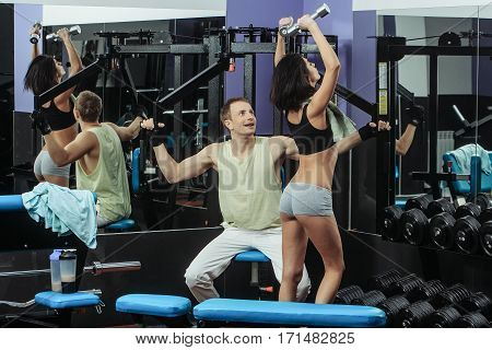 Muscular Man And Sexy Girl At Gym Trainer With Dumbbells