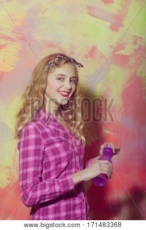 Cheerful Pretty Girl Smiles With Violet Water Bottle