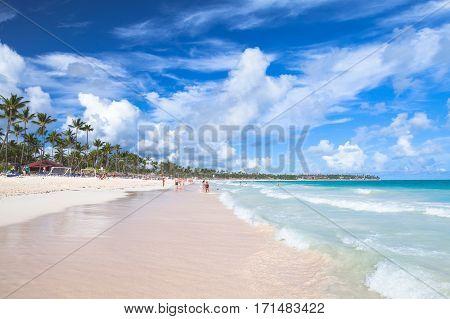 Bavaro beach Dominican republic - January 4 2017: Coastal Caribbean seascape. Atlantic ocean coast ordinary tourists rest on a sandy beach of Punta Cana resort