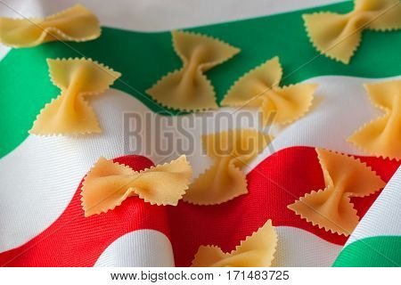 Dry Macaroni close-up on a background of colors of the Italian tricolor. Concept of Traditional Italian cuisine. For background use