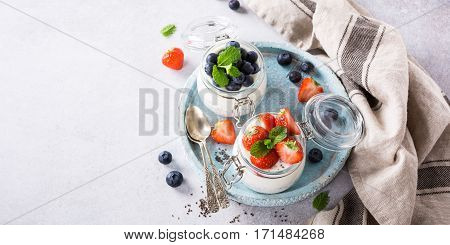 Chia Pudding for breakfast in glass jars garnished with berry in two portions on light gray stone background with a napkin and spoons. Copy space. Top view.