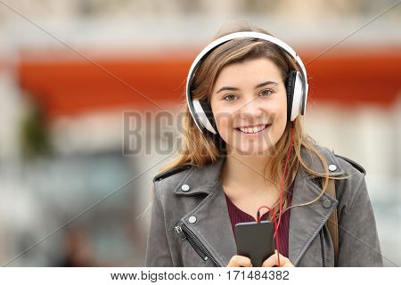 Front view of a happy young adult girl listening music on line with headphones and looking at you in the street