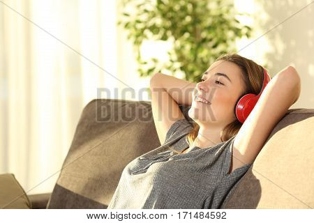 One relaxed teen resting and listening music with wireless headphones sitting on a sofa in the living room at home with a warm light
