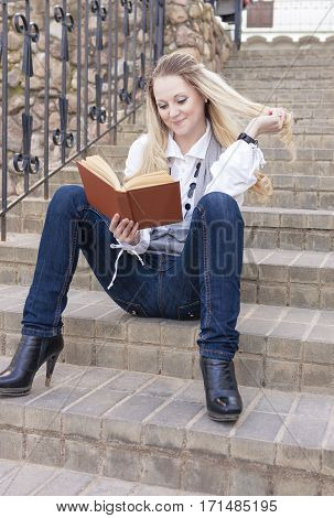 Portrait of Cute and Tranquil Caucasian Blond Woman Reading Book While Sitting Straight on Stairs Outdoors.Vertical Image