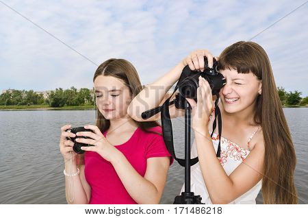 Two funny photographer teen girls outdoors by the river