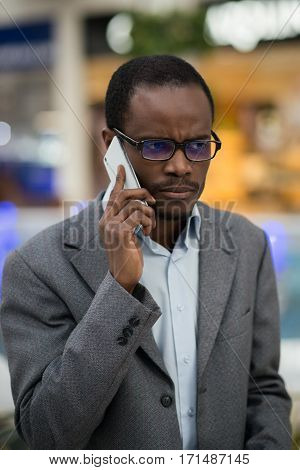 Afro-american man has serious conversation on the phone.