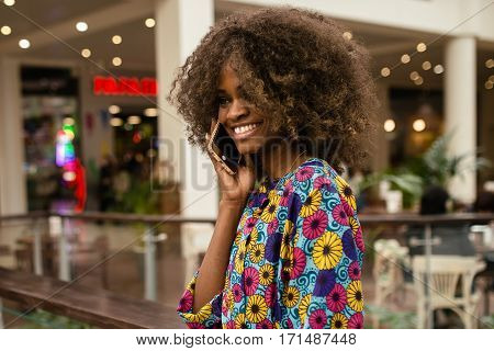 Afro-american woman talking on the phona and smiling, standing in a shopping mall.