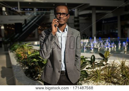 Good talk. Confident young African man talking on mobile phone and smiling while standing against grey background