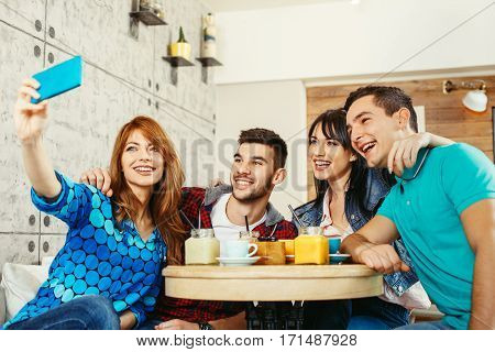 Group of young people having fun in cafe and doing selfie