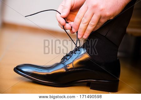 Groom putting his wedding shoes. Hands closeup.