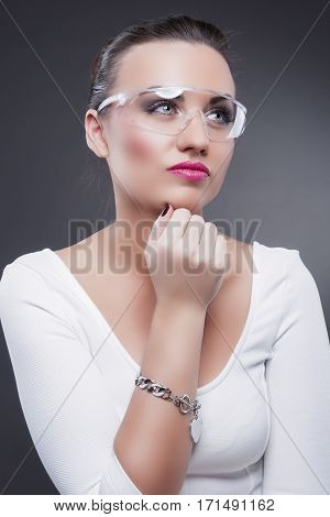 Fashion Concepts and Ideas. Closeup Portrait of Thinking Caucasian Brunette Woman in Glasses Against Gray Background. Vertical Shot