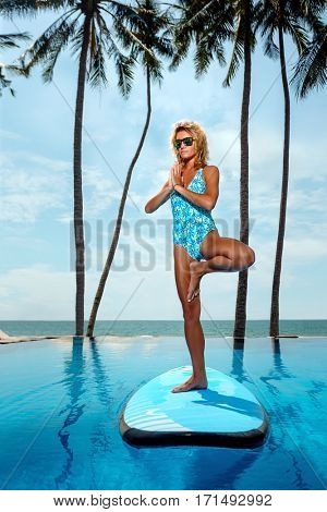 Yoga by woman on surfboard in swimming pool near the ocean