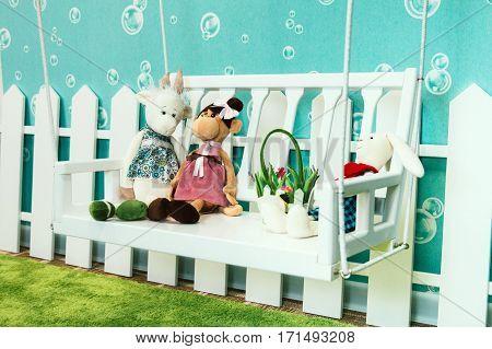 children's soft toys in the children's room light sitting on a swing