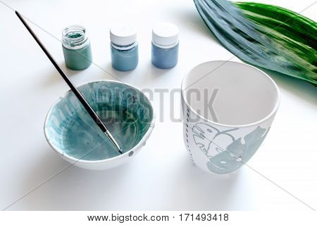 painted ceramic cup on white background close up
