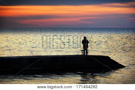 Fishermen fish at sunset on the Black Sea