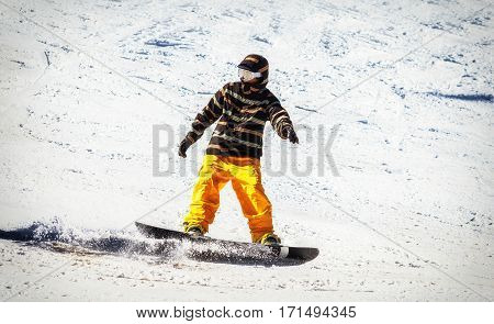 Yellow snowboarder descend from the high mountains