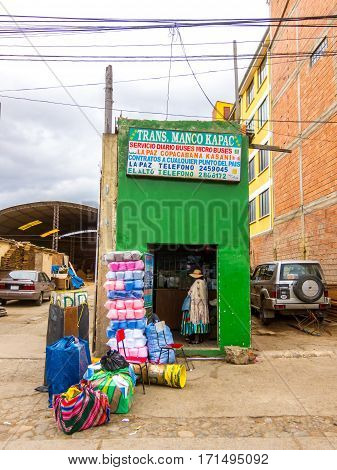 La Paz, Bolivia - December 7, 2011: Woman with many bags buying bus tickets in a curious shop in El Alto