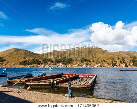 Tiquina, Bolivia - December 7, 2011: Several men working on rafts, handling planks in the bright noon sun