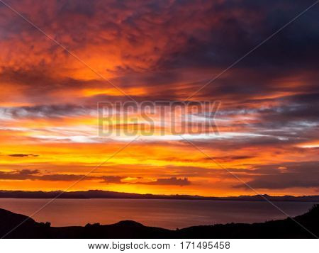 Sunset over Lake Titicaca with gorgeous reds and oranges