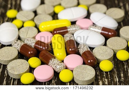 a set of tablets and pills for a speedy recovery and prevention of diseases. On wood background