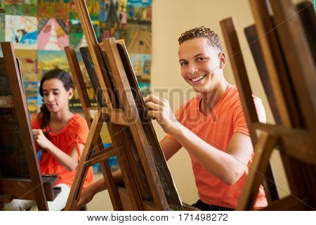 School of art college of arts education for group of students. Portraif of happy hispanic young man smiling looking at camera.