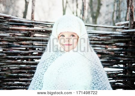 Little funny girl in a white downy shawl is woven at the fence
