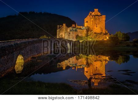 Eilean Donan Castle illuminated at night Scotland