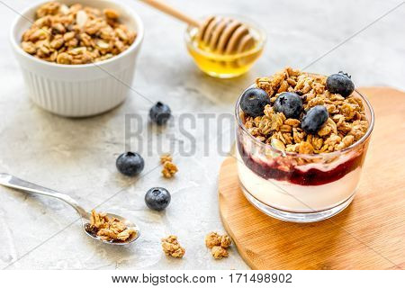 Healthy fitness breakfast from yoghurt with muesli and blue berries on kitchen table background