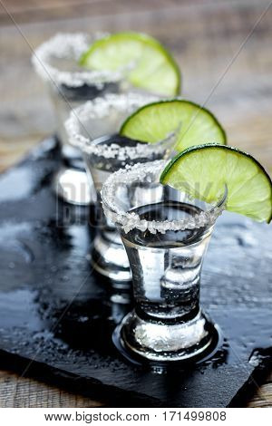 Bar set with silver tequila shots, fresh green lime and salt on wooden table background
