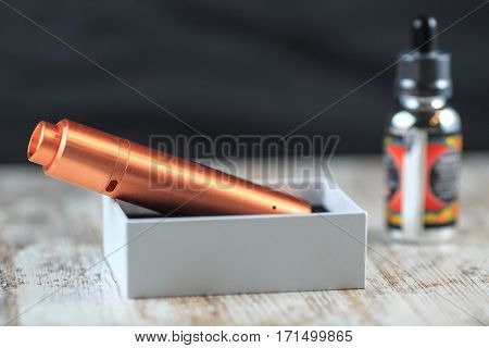Electronic Cigarette In White Box And A Bottle With Fluid. Mechanical Mod.