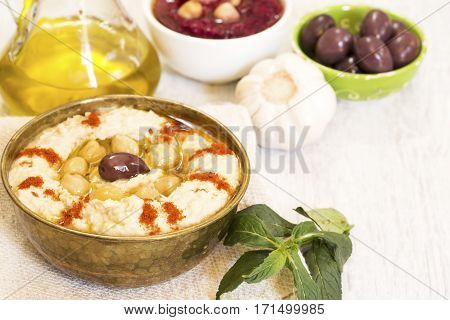 Hummus with olives garlic mint on white wooden background