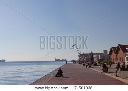 THESSALONIKI GREECE - DECEMBER 25 2015: People relaxing on the quay - pier of the old port of Thessaloniki a Greek flag can be seen in the background