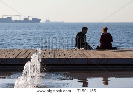 THESSALONIKI GREECE - DECEMBER 25 2015: People relaxing on Thessaloniki seafront and drinking